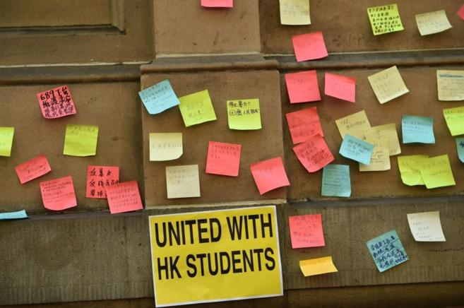 Notas a favor de los manifestantes de Hong Kong en una pared de...
