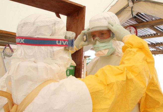 Dos sanitarios de MSF se ajustan el equipo protector.