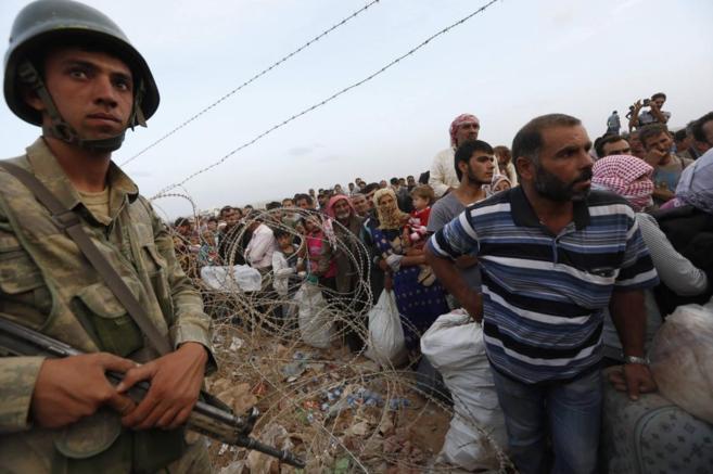 Un soldado turco monta guardia junto a una fila de refugiados kurdo...