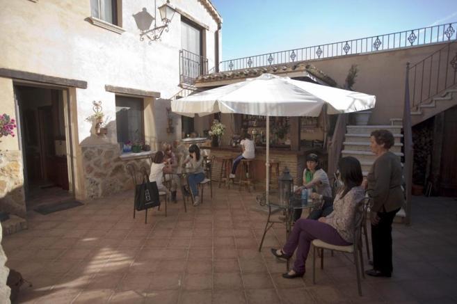 Un grupo de viajeros descansa en el patio de un alojamiento de turismo...