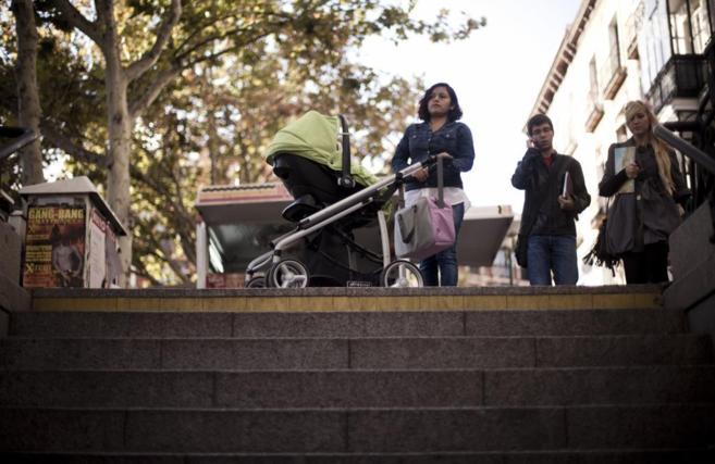 Una madre lleva un carrito con su bebé cerca de una boca de Metro en...