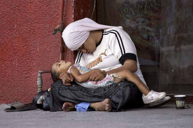 Una refugiada siria duerme con su hijo entre los brazos en una calle...