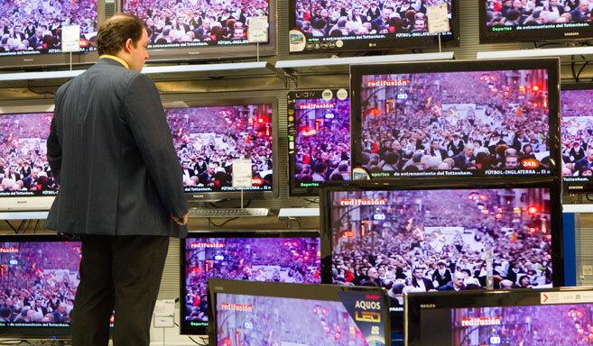 Un hombre mira varias pantallas de televisión en un establecimiento.