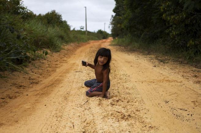 Un niño Ka'apor en una carretera que usan los madereros para...
