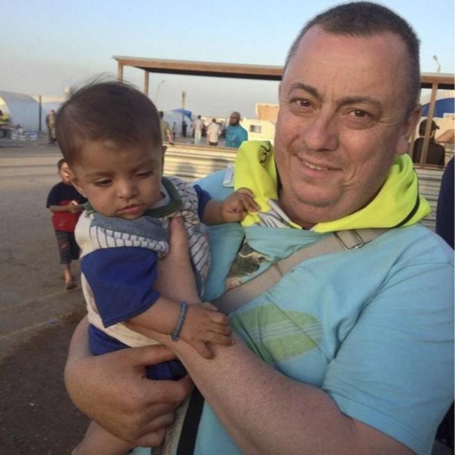 Alan Henning sostiene en brazos a un niño refugiado en la frontera...
