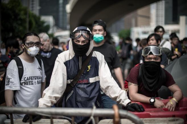 Varios jóvenes ocultan sus rostros durante las protestas de Hong...