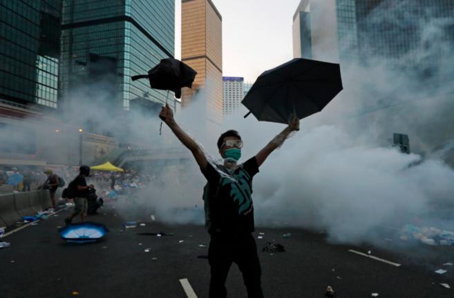 Manifestante con máscara y paraguas frente a los botes de gases...