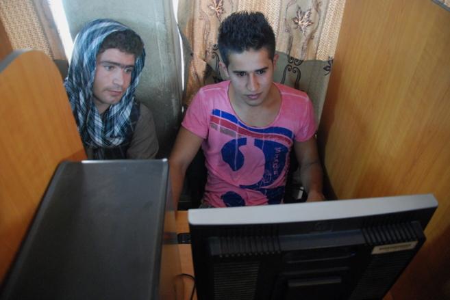 Dos jóvenes consultan sus cuentas de Facebook en un cibercafé en...