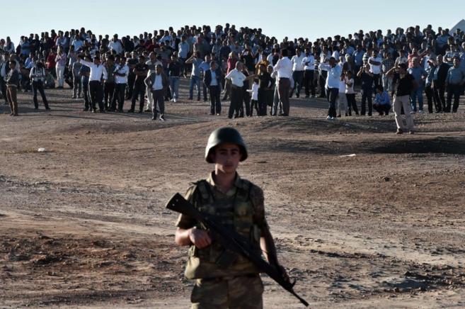 Un soldado monta guardia mientras manifestantes kurdos protestan en...