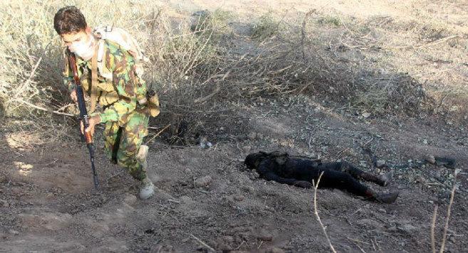 Un combatiente suní iraquí pasa junto al cadáver de un miliciano...