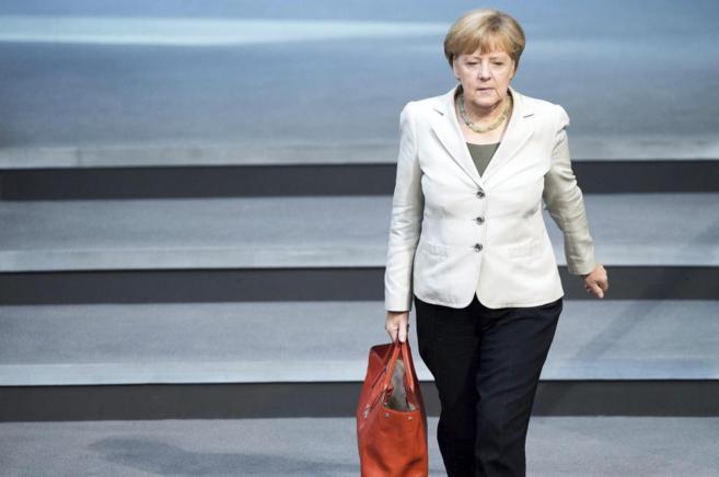 Angela Merkel andando con un bolso rojo tras la presentación de los...