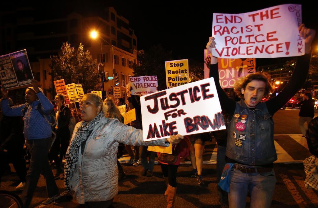 Varias personas caminan por las calles de Ferguson, ayer, pidiendo...
