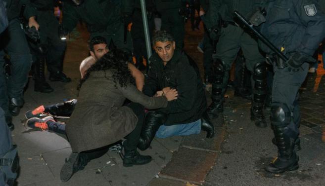 Un manifestante herido es protegido por los antidisturbios durante los...