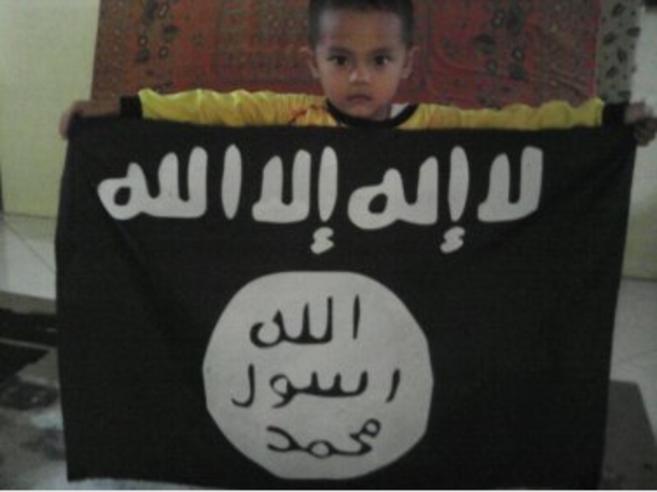 Un niño sostiene una bandera que hace apología del Estado Islámico.
