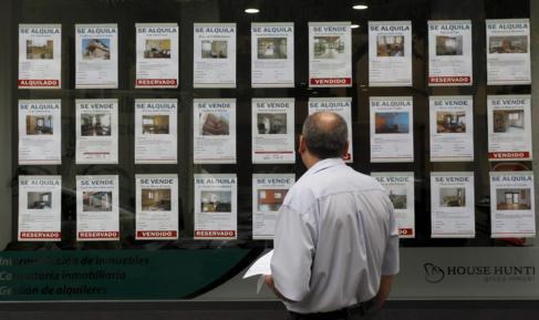 Un hombre mira los anuncios de un escaparate de una inmobiliaria.