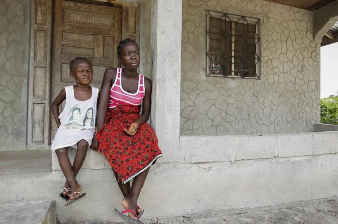 Huérfanos liberianos permanecen a las afueras de su casa tras...