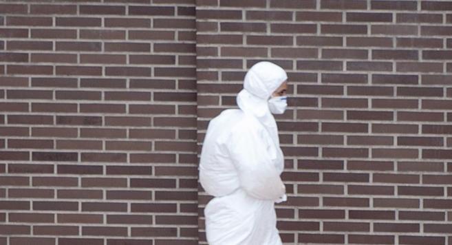 Uno de los trabajadores desinfectando el edificio donde vive la...