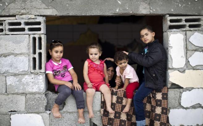 Varios niños sentados en una ventana de una casa a medio construir en...