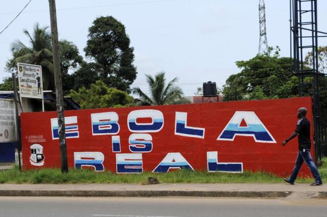 Un hombre camina frente a un muro en Monrovia (Liberia) en el que se...