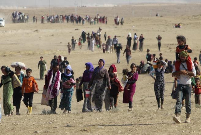 Mujeres, hombres y niños yazidíes huyen del IS en el norte de Irak.