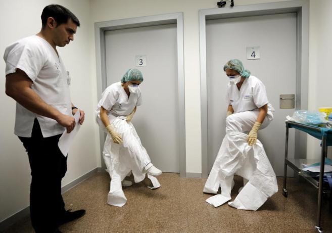 Dos auxiliaresse colocan los trajes de protección durante un curso en...