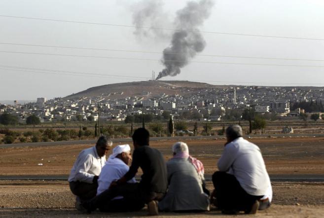 Unas personas observan desde la lejanía la ciudad kurda de Kobane,...
