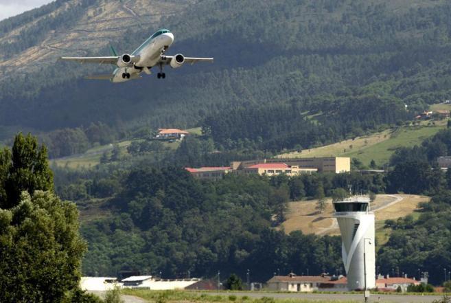 Un avión despegando ante una torre de control
