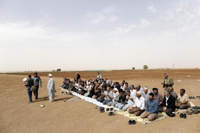 Un grupo de ciudadanos reza por los combatientes kurdo-sirios muertos...