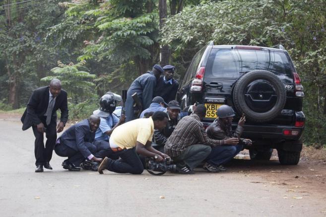 Refugiados tras un coche frente al centro comercial de Nairobi...