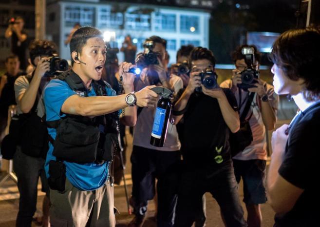 Un policía amenaza a un manifestante con un bote de gas pimienta.