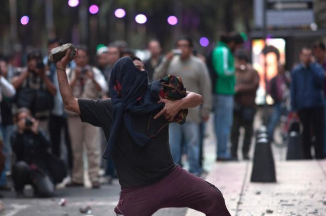 Un joven lanza una piedra a la fachada de la Fiscalía federal de la...