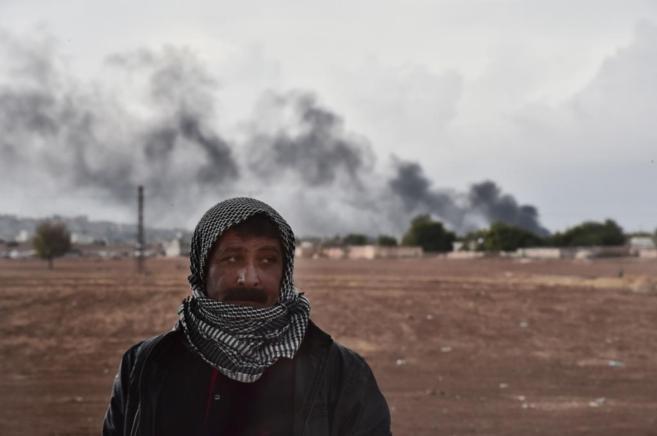 Un hombre kurdo en primer plano, a escasos metros de los bombardeos en...