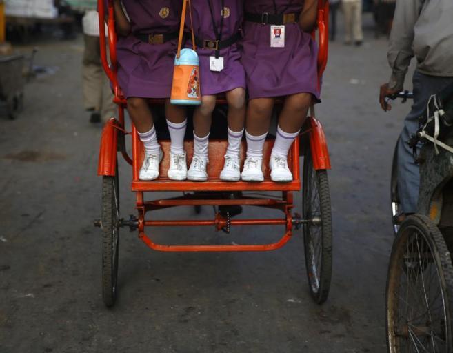 Tres niñas indias se dirigen al colegio en un 'rickshaw' en...