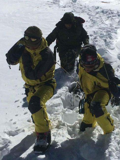 Miembros del Ejército nepalí retiran el cadáver de un excursionista...