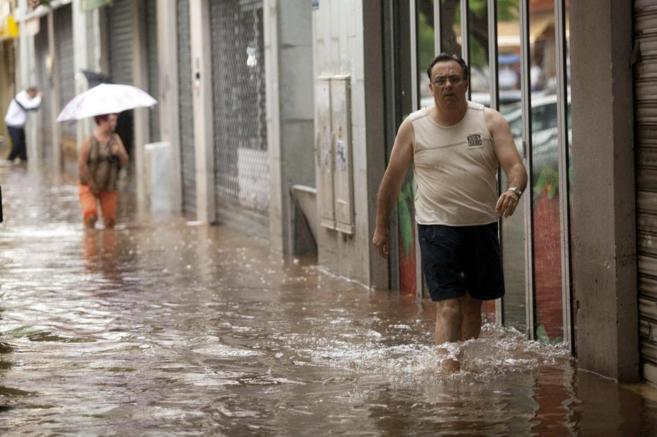 Transeúntes en una calle inundada en Santa Cruz.