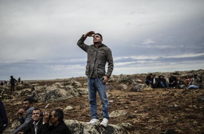 Ciudadanos kurdos miran al cielo en la ciudad de Kobane