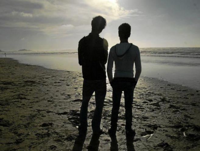 Una pareja de gays, de espaldas, en la playa de Casablanca