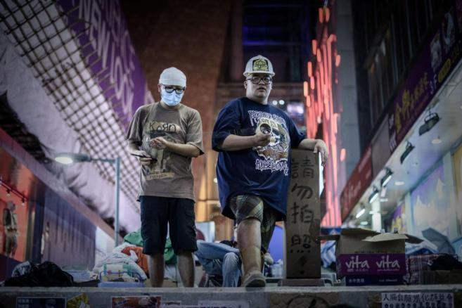 Dos manifestantes pro-democracia en el distrito de Mongkok, en Hong...