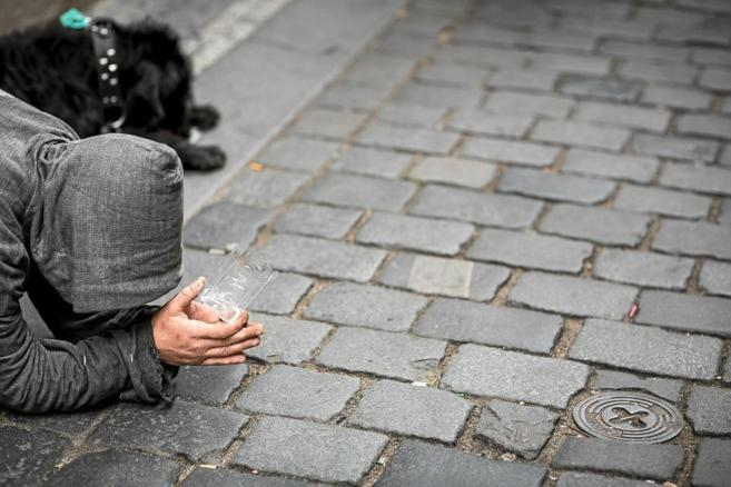 Un hombre pide limosna en la calle