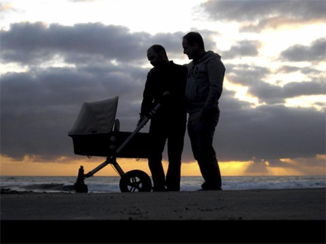 Una pareja con su hija, nacida por vientre de alquiler, pasea por una...