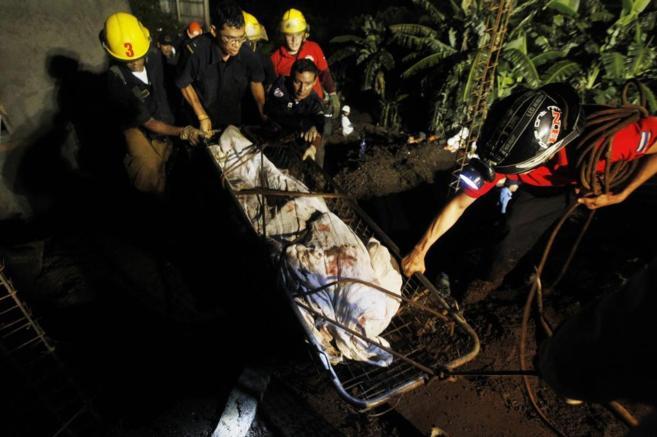 Varios rescatadores recuperan un cuerpo en Managua