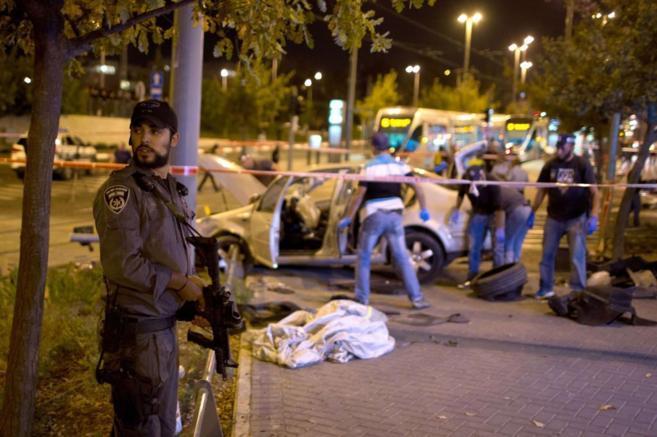 Un policía israelí cubre la zona del atentado mientras se...