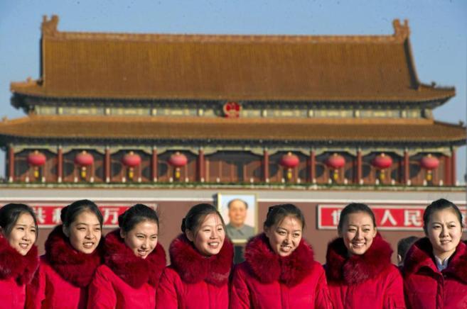 Varias azafatas, ante el retrato de Mao Zedong que preside la Plaza de...
