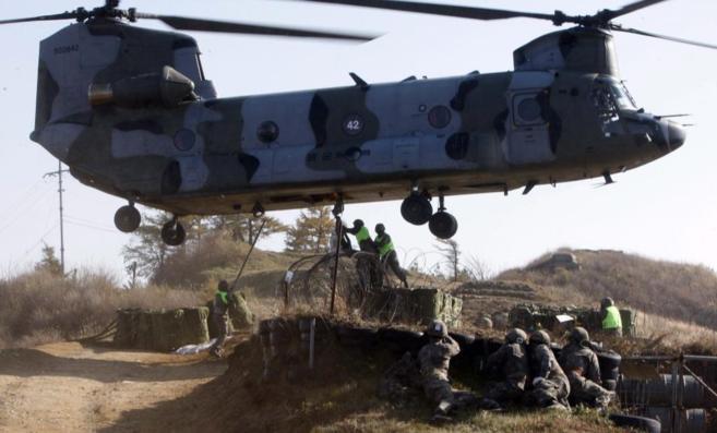 Un helicóptero distribuye comida y otros suplementos a una unidad del...