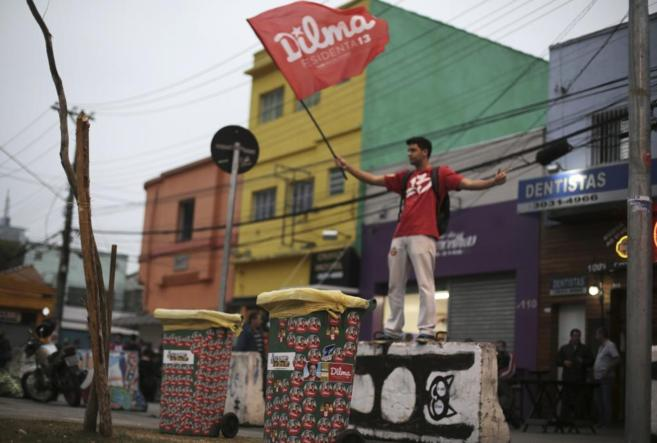 Un joven con una bandera de Dilma, en una favela de Brasil.