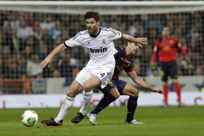 Xabi Alonso y Xavi Hernández pugnan por el control del balón en uno...