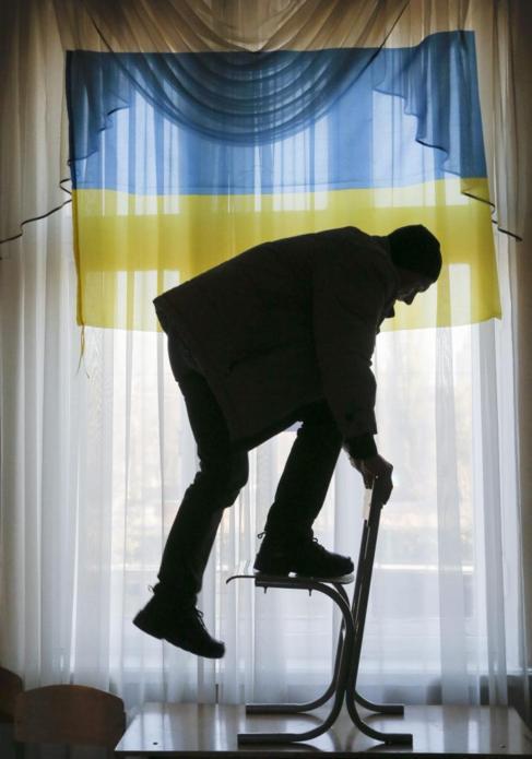 Un miembro del comité electoral coloca la bandera ucraniana en un...