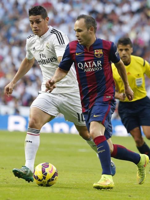 Iniesta controla un balón ante la presión de James Rodríguez.