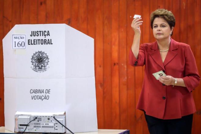 Dilma, con la papeleta en la mano, al votar, esta mañana.