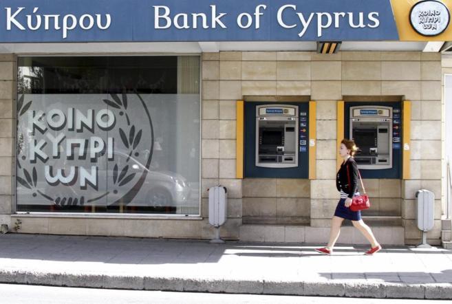 Una mujer pasa por delante de una sucursal del Banco de Chipre